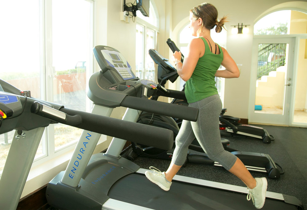 Woman running on treadmill at the fitness center.